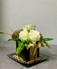 Gift-wrapped vase of winter flowers and pine cones with gold accents