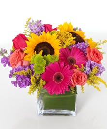 Sunflowers and a variety of pink and purple flowers in a glass cube vase.