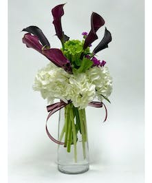 White hydrangea & hot pink calla lilies in a glass vase.