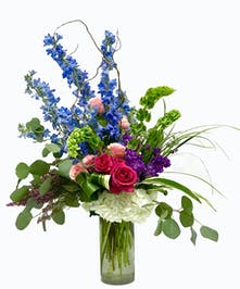 Blue, hot pink and white flowers with eucalyptus in a glass cylinder vase.