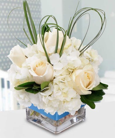 White and blue hydrangea, roses and greenery in a clear glass cube vase tied with blue ribbon.