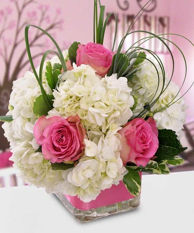 Pink and white flowers in a glass cube vase with pink ribbon.