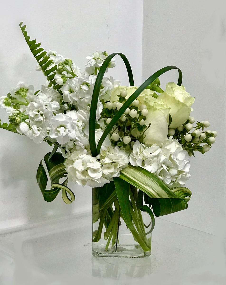 All white flowers in a glass cube