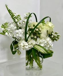 All white flowers in a glass cube vase with greenery.