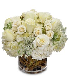 All-white flowers in a clear glass vase with accents.