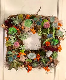 Square-shaped door wreath of living succulents, moss, greenery and accents.