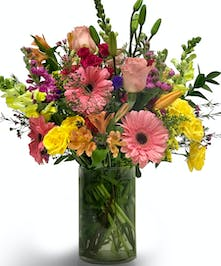 Mix of pink, purple and yellow flowers in a clear glass vase.