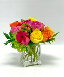 Ten brightly colored roses in a glass cube vase.