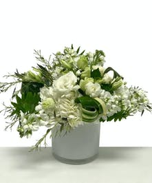 All white flower design in a glass cube vase.