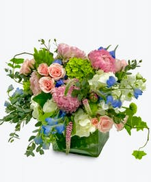 Pink and peach blooms with green and blue garden flowers in a glass cube vase.