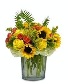 Sunflowers, roses and fern in a clear glass vase.