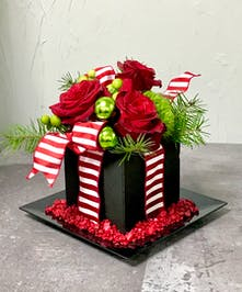 Reed roses, green glass ornaments and more in black floral foam tied with a red and white striped bow