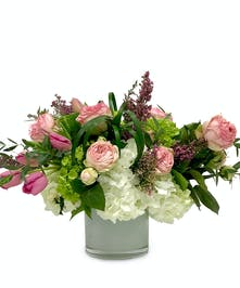 Garden roses, tulips and hydrangea in a white glass vase.