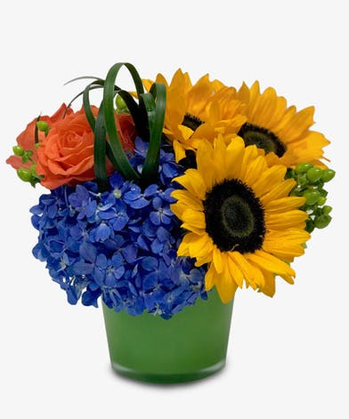 Sunflowers, orange roses, hydrangea, and more in a green glass vase.