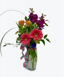 Seasonal flowers in complementary colors designed in a clear glass vase