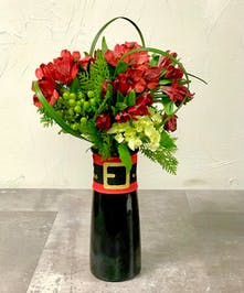 Red Peruvian lilies in a glass vase tied with raffia
