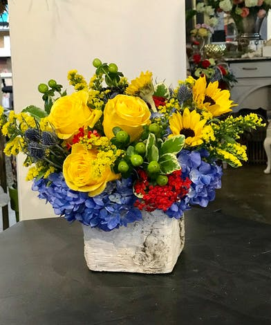 A bright mix of yellow and blue flowers with berries in a clear glass cube vase.