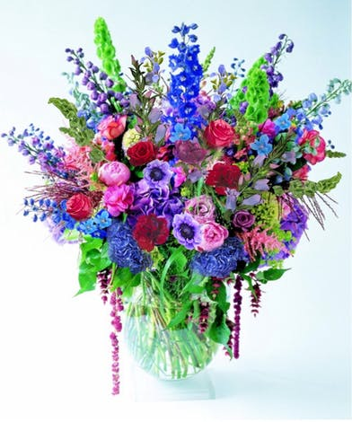 Large vase of all seasonal flowers in shades of blue, lavender and pink.