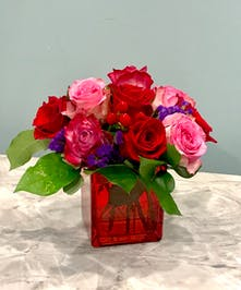 Ten roses in red and purple with green accent flowers in a leaf-lined vase.