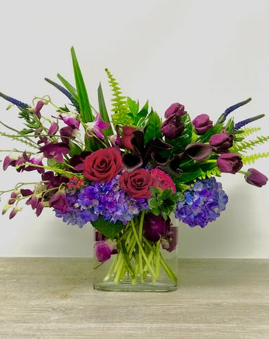Flowers in purples, reds and blues in a clear glass vase.