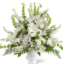 All-white seasonal flowers in a white urn.