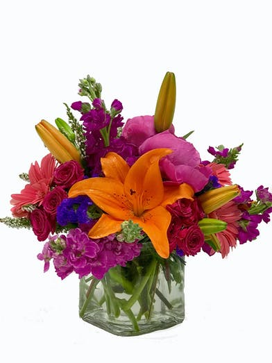 Vibrant hot pink, orange, green and purple flowers in a clear glass cube vase.