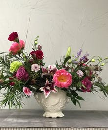 Winter greenery and flowers in shades of plum, raspberry and coral in a unique white vase