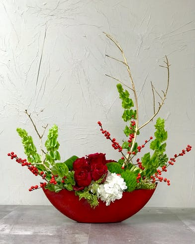 Red resin vase filled with bells of Ireland, gold accents, red roses and hydrangea