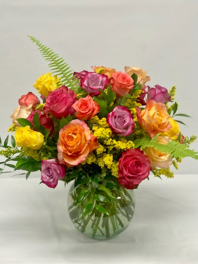 Assorted colored roses in a clear glass vase.