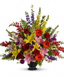 Sympathy urn filled with seasonal flowers in bright colors.