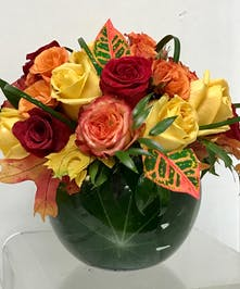 Roses in fall colors in a bubble bowl vase.