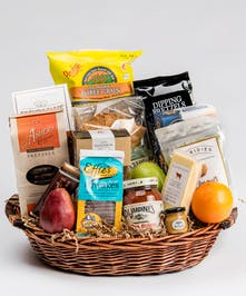 Gift basket filled with chips, pretzels, cheese and fruit.
