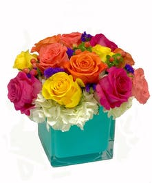 Vibrant colored roses nestled in a bed of white hydrangea and gathered in a colorful cube.