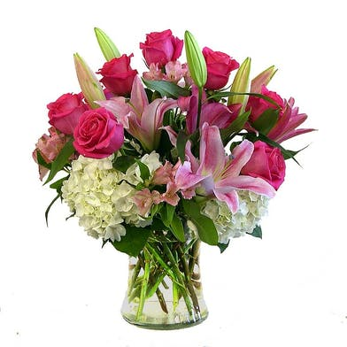 Oriental lilies, hydrangeas and roses in a clear glass vase.