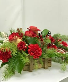 Holiday centerpiece of roses, carnations, berries, winter greenery and more in a wooden crate