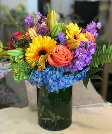 Bright mix of flowers in a clear glass vase.