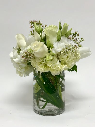 Elegant all-white sympathy flowers in a clear glass vase.