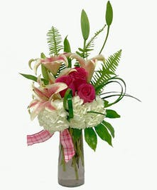 Hydrangea, lilies & roses in a clear glass vase.