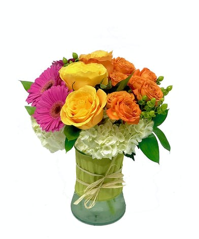 Orange, yellow and hot pink flowers in a clear glass vase tied with ribbon.