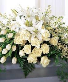 Casket spray of all-white seasonal flowers.