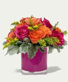 Ten roses in bright orange, yellow and chartreuse in a hot pink glass cylinder.