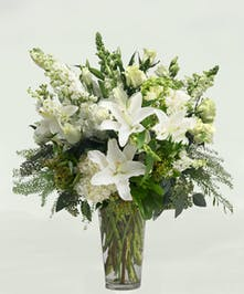 Glass vase filled with premium white and cream flowers.