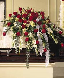 Casket spray of red and white flowers.