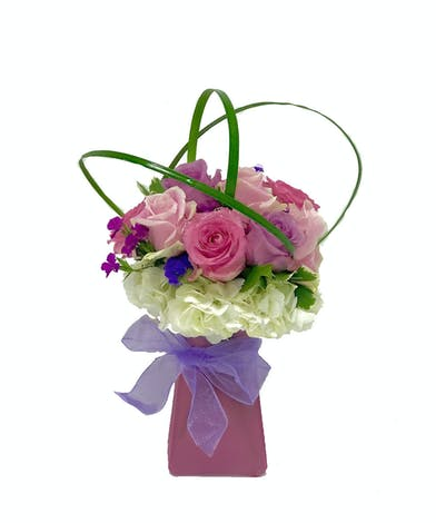 Pink trapezoid vase filled with pastel roses and tied with purple ribbon.