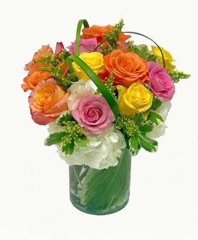One dozen roses in assorted colors with hydrangea in a leaf lined vase.