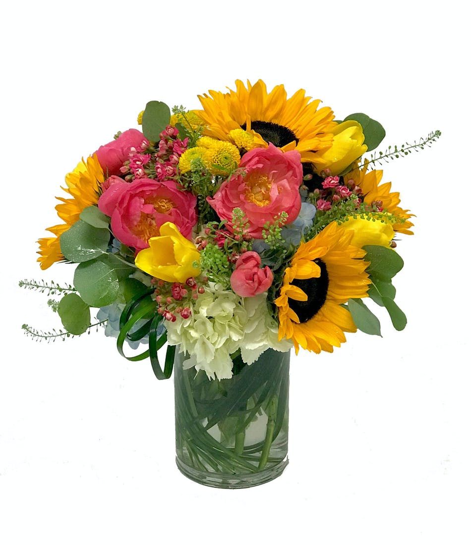 Sunflowers and peonies in a leaf lined vase.
