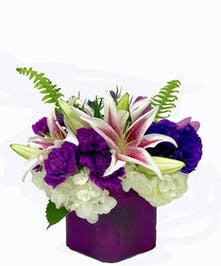 Purple glass cube of purple carnations, lisianthus, roses, hydrangea and lilies.