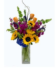 Sunflowers, tulips, stock, and hydrangea in a clear glass vase.