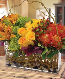Roses, lilies, hydrangea and pincushion protea in a rectangular vase.