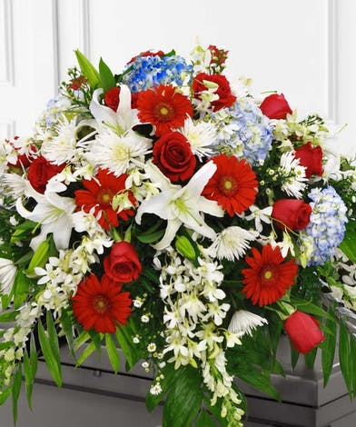 Patriotic casket display of red, white and blue flowers.